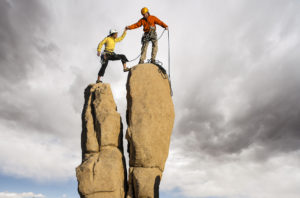 Team of climbers struggle to the summit of a challenging pinnacle.